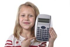 Belles années femelles douces de l'enfant 6 à 8 tenant des fournitures scolaires de calculatrice Photos libres de droits