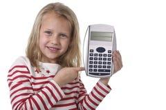 Belles années femelles douces de l'enfant 6 à 8 tenant des fournitures scolaires de calculatrice Photographie stock libre de droits