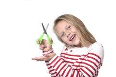 Belles années femelles douces de l'enfant 6 à 8 tenant le concept de fournitures scolaires de ciseaux de coupe Photo libre de droits