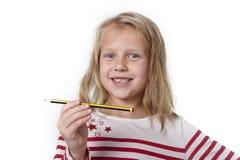 Belles années femelles douces de l'enfant 6 à 8 tenant le concept de fournitures scolaires de crayon Photo libre de droits
