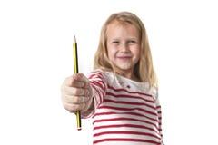 Belles années femelles douces de l'enfant 6 à 8 tenant le concept de fournitures scolaires de crayon Images libres de droits