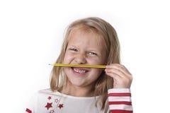 Belles années femelles douces de l'enfant 6 à 8 tenant le concept de fournitures scolaires de crayon Photographie stock libre de droits