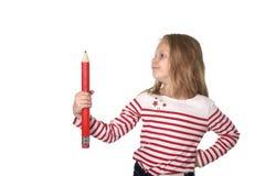 Belles années femelles douces de l'enfant 6 à 8 tenant le concept rouge énorme de fournitures scolaires de stylo Image libre de droits