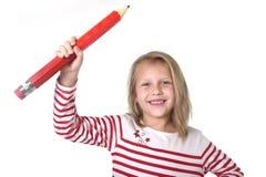 Belles années femelles douces de l'enfant 6 à 8 tenant le concept rouge énorme de fournitures scolaires de stylo Photographie stock