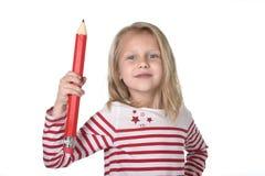 Belles années femelles douces de l'enfant 6 à 8 tenant le concept rouge énorme de fournitures scolaires de stylo Photos libres de droits