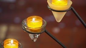 Belles bougies jaunes de brûlure dans l'église banque de vidéos