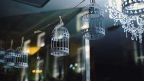 Belles cages à oiseaux décoratives accrochant sur une corde banque de vidéos