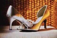 Belles chaussures argentées de femmes de couleur avec la décoration de bijoux sur le coussin avec le fond en bois d'armure image stock