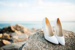 Belles chaussures nuptiales sur les roches photos stock