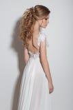 Belles coiffures à la mode pour la belle jeune mariée sensible de jeunes filles dans une belle robe de mariage sur un fond blanc  Photos libres de droits