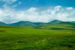 Belles collines vertes avec des nuages et des montagnes sur le fond Photo libre de droits