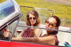 Belles dames avec des verres de soleil posant dans une voiture de vintage en été de ressort de jour ensoleillé Images stock