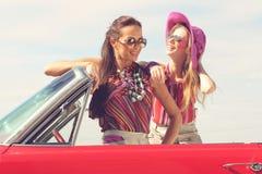 Belles dames avec des verres de soleil posant dans une voiture de vintage en été de ressort de jour ensoleillé Images libres de droits