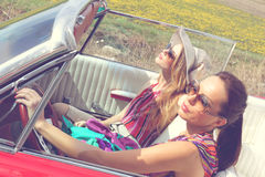 Belles dames avec des verres de soleil posant dans une voiture de vintage en été de ressort de jour ensoleillé Photo stock