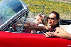 Belles dames avec des verres de soleil posant dans une voiture de vintage en été de ressort de jour ensoleillé Photographie stock