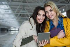 Belles dames avec le dispositif et les livres regardant avec joie photographie stock