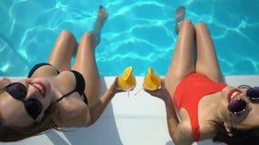 Belles dames faisant tinter des cocktails et jouant avec de l'eau, regardant dans la caméra banque de vidéos