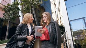 Belles deux étudiantes utilisant nouvelles de lecture de tablette de bonnes, dépensant la pause de midi avec plaisir dans clips vidéos
