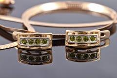 Belles et élégantes boucles d'oreille d'or avec des émeraudes Photographie stock