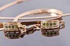 Belles et élégantes boucles d'oreille d'or avec des émeraudes et un pendant Image stock