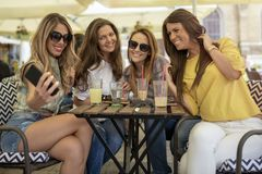 Belles et jolies filles ayant l'amusement en café Filles prenant l'individu photos libres de droits