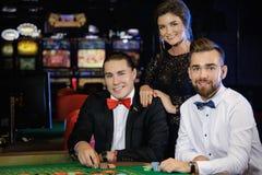 Belles et riches personnes jouant la roulette dans le casino Images libres de droits