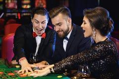 Belles et riches personnes jouant la roulette dans le casino Photo libre de droits