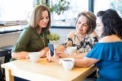 Belles femmes à l'aide d'un téléphone portable au café Image stock