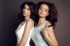 Belles femmes avec du charme avec les cheveux foncés dans des robes élégantes Image stock