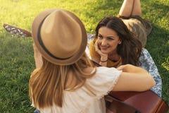 Belles femmes ayant l'amusement jouant la guitare dans le parc Photos stock
