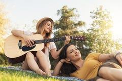 Belles femmes ayant l'amusement jouant la guitare dans le parc Images libres de droits