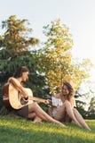 Belles femmes ayant l'amusement jouant la guitare dans le parc Photographie stock libre de droits