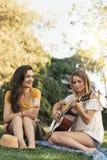 Belles femmes ayant l'amusement jouant la guitare dans le parc Image stock