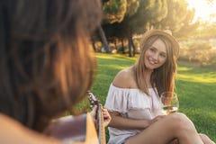 Belles femmes ayant l'amusement jouant la guitare dans le parc Image libre de droits