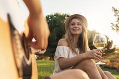 Belles femmes ayant l'amusement jouant la guitare dans le parc Photos libres de droits