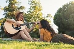 Belles femmes ayant l'amusement jouant la guitare dans le parc Photo stock