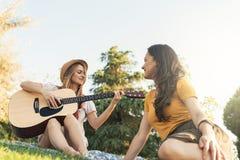 Belles femmes ayant l'amusement jouant la guitare dans le parc Images stock
