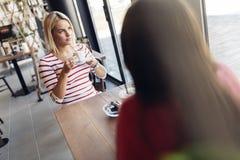 Belles femmes buvant le café et le bavardage Photographie stock libre de droits