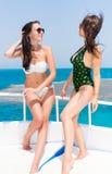Belles femmes dans le maillot de bain se tenant sur le yacht à une somme ensoleillée Images stock