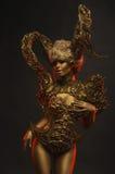 Belles femmes de diable avec les klaxons ornementaux d'or Photo libre de droits