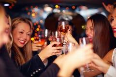 Belles femmes faisant tinter des verres dans la limousine Images libres de droits