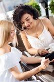Belles femmes gaies regardant l'écran de comprimé Photographie stock libre de droits