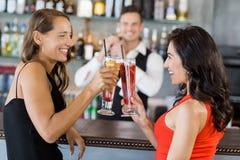 Belles femmes grillant des verres de cocktail Photographie stock libre de droits
