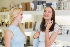 Belles femmes heureuses pulvérisant le parfum Photo libre de droits