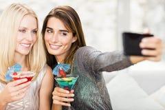 Belles femmes prenant le selfie avec le téléphone portable Photos stock
