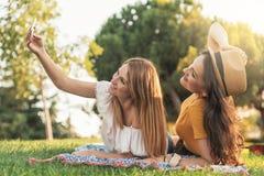 Belles femmes prenant un portrait de selfie en parc Photo stock