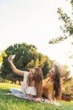 Belles femmes prenant un portrait de selfie en parc Image libre de droits