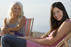 Belles femmes s'asseyant sur des chaises longues à la plage Photos stock