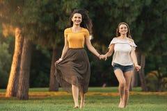 Belles femmes souriant et ayant l'amusement et le fonctionnement en parc Image libre de droits