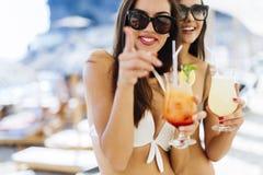 Belles femmes sur la plage appréciant des cocktails Photos libres de droits